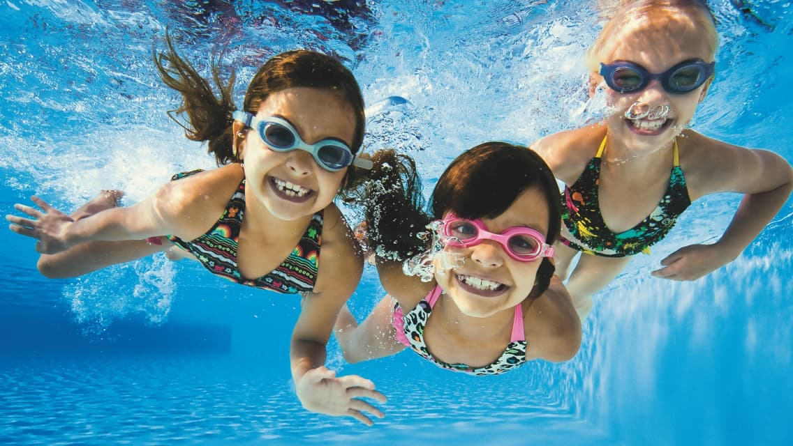 Three young girls smiling while swimming underwater in the pool with goggles on