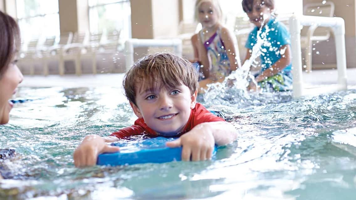 Young boy swimming in pool with kickboard alongside instructor with friends smiling while watching