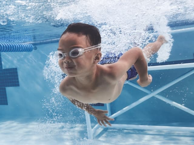 Young boy swimming underwater with goggles on